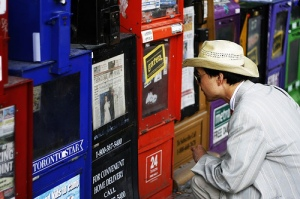 Someone reading headlines in news boxes